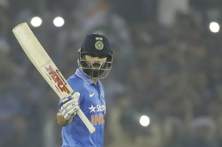 India's Virat Kohli raises his bat after scoring a century during their third one-day international cricket match against New Zealand in Mohali, India, Sunday, Oct. 23, 2016. (AP Photo/Tsering Topgyal)
